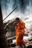 Pensive Buddhist monks walking around waterfall. Pensive Buddhist monks walking near waterfall stock images