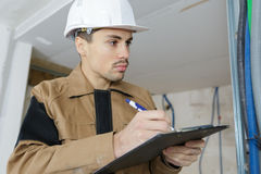 Pensive builder standing with clipboard in hands Stock Photo