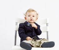 Pensive business baby. Pensive office baby dressed in business outfit with a bow and mobile phone in his hand Stock Photos