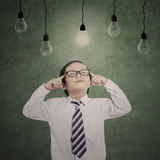Pensive business child under lit bulbs Royalty Free Stock Image