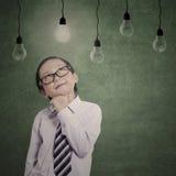 Pensive business kid under lit lightbulbs Royalty Free Stock Images