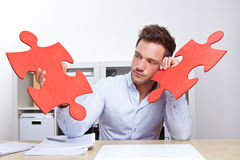 Pensive business man with jigsaw. Pensive business man with two oversized red jigsaw puzzle pieces in office Stock Photography