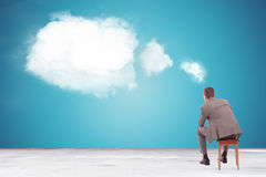 Pensive business man looking at a speech bubble. Back view of a pensive business man looking at a speech bubble made of clouds Royalty Free Stock Image