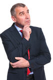 Pensive business man looks away. Pensive middle aged business man looking away from camera while holding his hand at his chin. isolated on a white background Royalty Free Stock Photography