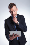 Pensive business man looks at tablet Stock Photo