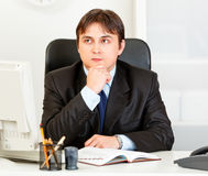 Pensive business man planning timetable in diary Royalty Free Stock Photo