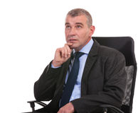 Pensive business man sits on chair and looks away Royalty Free Stock Image