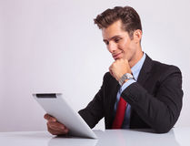 Pensive business man on tablet Stock Image