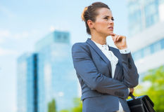 Pensive business woman with briefcase in office district Stock Photo