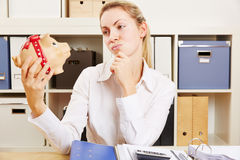 Pensive business woman lookinh at piggy bank Royalty Free Stock Photo