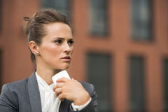 Pensive business woman near office building talking smartphone Royalty Free Stock Photos
