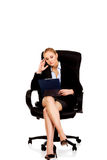 Pensive business woman sitting on armchair and reading notes Royalty Free Stock Photography