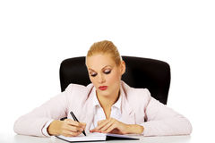 Pensive business woman taking notes behind the desk Stock Photos