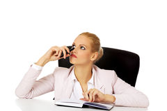 Pensive business woman taking notes behind the desk Royalty Free Stock Image