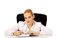 Pensive business woman taking notes behind the desk Royalty Free Stock Photo
