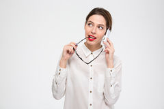 Pensive business woman talking on mobile phone and holding glasses. Smiling pensive young business woman talking on mobile phone and holding glasses in her hand Stock Images