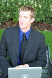 Pensive businessman. Close-up waist-up view of young blue blond hair businessman sitting on bench holding laptop looking away Stock Photos