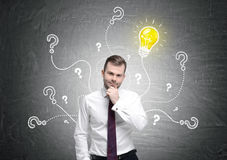 Pensive businessman, bulb and questions Stock Image