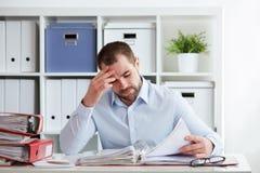 Pensive businessman calculates taxes Stock Image