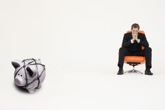 Pensive businessman on chair and piggybank tied with rope representing financial difficulties Stock Photos