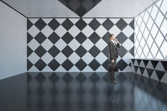 Pensive businessman in chessboard interior Stock Photography