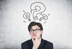 Pensive businessman in glasses, questions Stock Photos