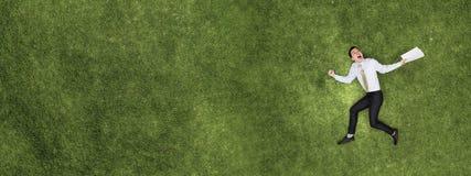 Pensive businessman on grass stock image