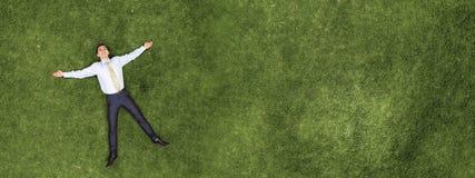 Pensive businessman on grass stock photo