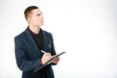 Pensive businessman holding clipboard and looking up Royalty Free Stock Images