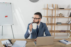 Businessman holding coffee cup while sitting at workplace with laptop in office Royalty Free Stock Image
