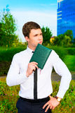 Pensive businessman. Holding notebook and looking into the distance in the park Royalty Free Stock Image