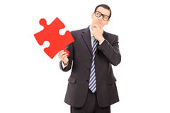 Pensive businessman holding a piece of puzzle Stock Images