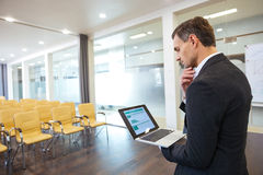 Pensive businessman with laptop standing in empty conference hall Royalty Free Stock Photo