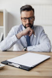 Pensive businessman looking at blank papers on table. Selective focus of pensive businessman looking at blank papers on table Stock Photos