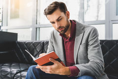 Pensive businessman making notes in writing-pad Royalty Free Stock Images