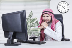 Pensive businessman with money out of computer. Portrait of pensive middle eastern male entrepreneur looking at money out of computer while sitting in the Royalty Free Stock Photography