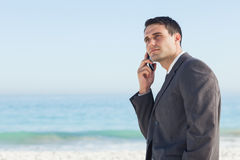 Pensive businessman on the phone. At the beach Stock Photo
