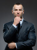 Pensive businessman props head with hand Stock Image