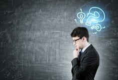 Pensive businessman, question marks Stock Photos
