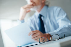 Pensive businessman reading a contract Stock Photos