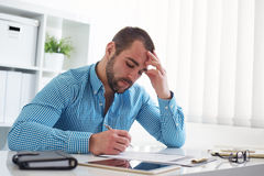 Pensive businessman signs a document Stock Photography