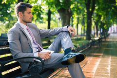 Pensive businessman sitting on the bench. Portrait of a pensive businessman sitting on the bench outdoors in park and holding tablet computer Royalty Free Stock Photo