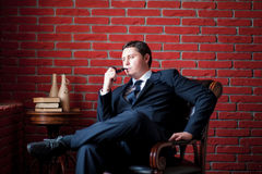Pensive businessman sitting on a chair Royalty Free Stock Image
