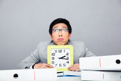 Pensive businessman sitting with clock Stock Images