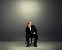 Pensive businessman sitting on office chair Stock Photos