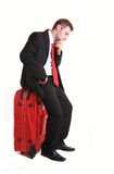 Pensive businessman sitting on red luggage Stock Photography