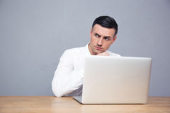 Pensive businessman sitting at the table with laptop Stock Photo