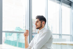 Pensive businessman sitting and thinking in office Royalty Free Stock Images