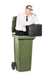 Pensive businessman standing inside a trash can Stock Photography