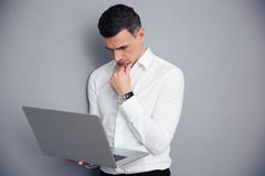 Pensive businessman standing with laptop Stock Photo